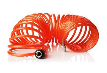 compressed air hose: Orange red thin spiral air hose used for pneumatic tools. Isolated on white with natural reflection.