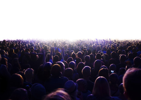 people from behind: Audience is watching a luminous surface.