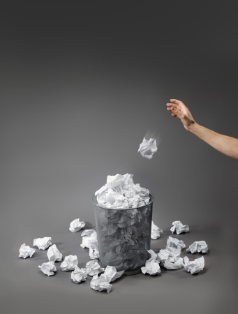 too much: Hand throwing a crumpled paper into a waste paper basket. Stock Photo