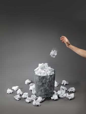waste paper: Mano que lanza un papel arrugado en una papelera.