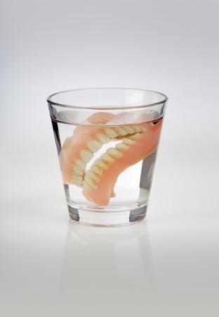 dientes sucios: Dentaduras viejas en un vaso de agua.
