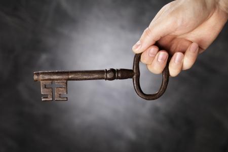 old keys: Man holding big antique skeleton key in his hand. Stock Photo