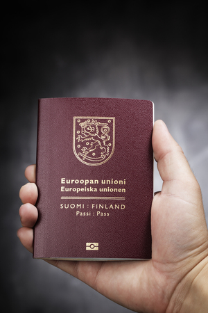 Hand holding a Finnish (Finland) passport. This is the new (2013) design of the passport. Stock Photo - 22436878