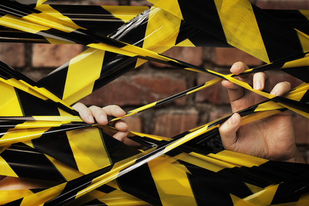 A Person behind yellow and black barrier tape.