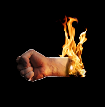 A burning fisted hand on black background Stock Photo - 23303926