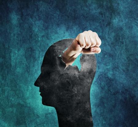 Conceptueel beeld van een vuist ponsen door een kartonnen hoofd