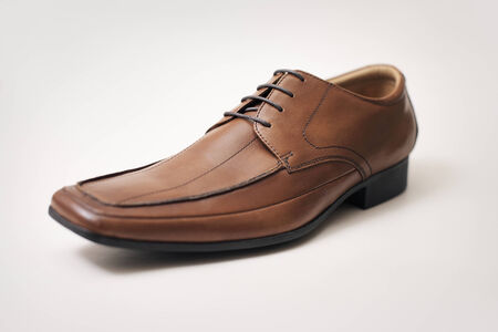mens shoes: Mens brown leather shoe on light brown wall  Stock Photo