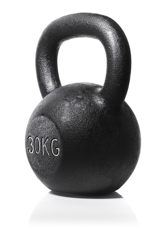 A rough and tough heavy 30 kg 66 lbs cast iron kettlebell isolated on white with natural reflection. Stock Photo