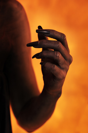 body paint: Female hand with black body paint and fake fingernails.