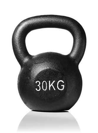 kg: A rough and tough heavy 30 kg 66 lbs cast iron kettlebell isolated on white with natural reflection. Stock Photo