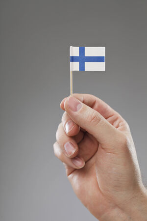 flagging: Man holding a tiny Finnish flag in his hand.