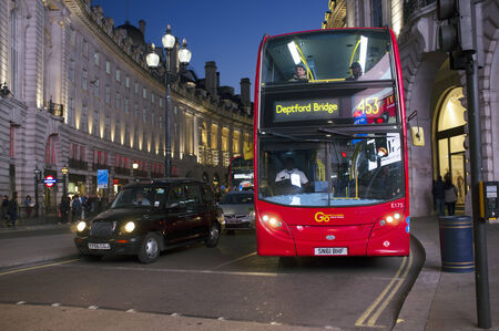 piccadilly: LONDON, UK – APRIL 16, 2014: London transport, Black taxi cab and red double-decker bus at Piccadilly Circus.