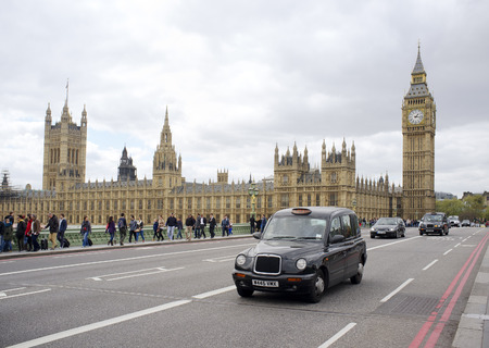 black cab: LONDON, UK – APRIL 18, 2014: Black taxi cab in front of the Palace of Westminster.