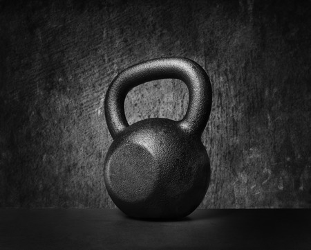 Black and whit image of a rough and tough heavy 30 kg 66 lbs cast iron kettlebell. Standard-Bild