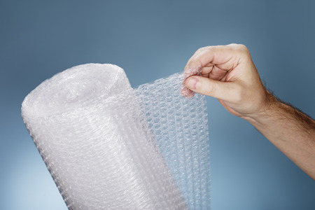 plastics: Man holding a roll of plastic bubble pack Stock Photo
