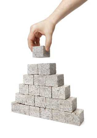 Man building pyramid made of small blocks of granite rock. photo