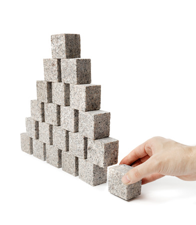 removing the risk: Hand removing the corner stone of a pyramid made of small granite rock blocks.