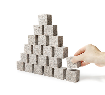 Hand removing one block of a pyramid made of small granite rock blocks.