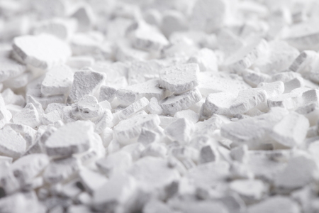 desiccation: Calcium chloride (CaCl2) flakes. Common applications include brine for refrigeration plants, ice and dust control on roads, and desiccation. Stock Photo