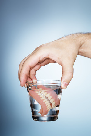 false teeth: Man holding a glass containing old dentures.