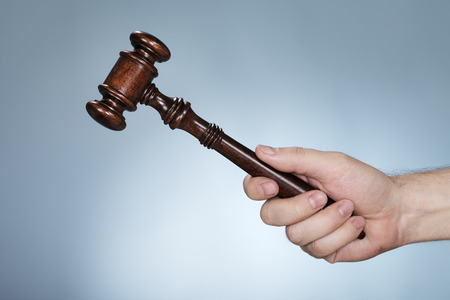 auctioneer: Man holding a mahogany gavel in his hand.