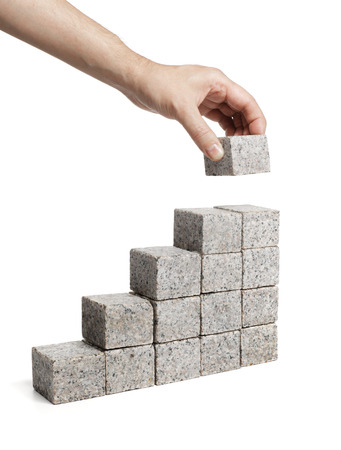 build up: Man stacking blocks made of granite rock. Stock Photo