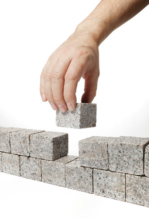 adds: Man building a wall made of small blocks of granite rock.