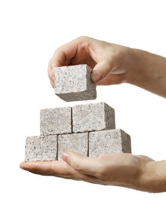 Man stacking small blocks of granite rock in his hands. photo
