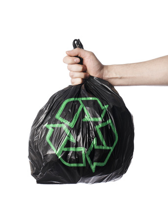 Man holding a black trash back with green Recycling symbol. photo