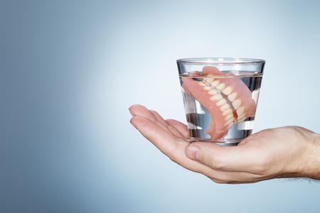 Homme tenant un verre contenant vieux dentier. Banque d'images
