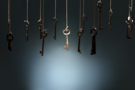 Old keys hanging on strings. One key in the middle is in spotlight focus.