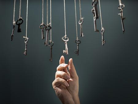 手は他のものの間で掛かるキーを選択します。 写真素材
