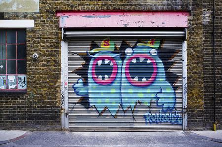 LONDON, UK - APRIL 18, 2014: Graffiti, posters and stickers on Fashion Street, Spitalfields  Whitechapel.