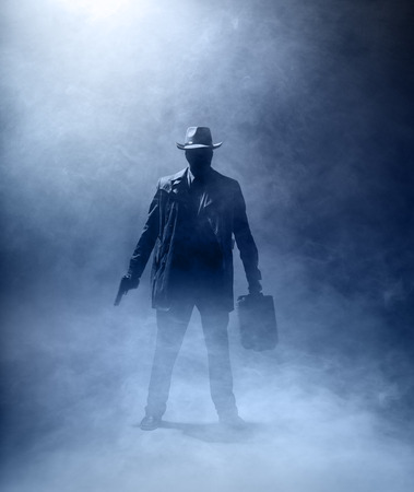 Faceles man with a gun and a briefcase standing in the fog.