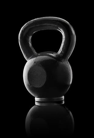 reflective background: Black metallic kettlebell on black reflective background.