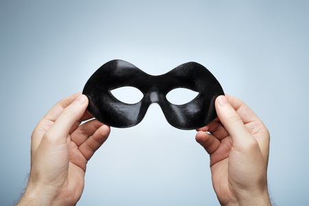 objects: Man holding a black eye mask in his hands.