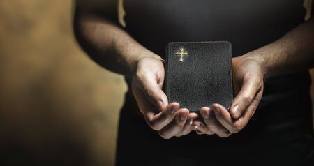black grip: Man holding an old small black bible in his hands. Short depth of field, the sharpness is in the cross.