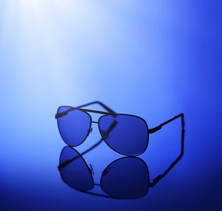 reflective: Sunglasses in blue light on a reflective background. Stock Photo