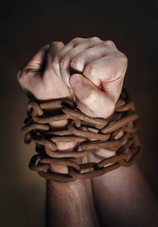 restraints: Hands of a man with a rusty chain around the wrists. Short depth of field, the sharpness is in the fist. Stock Photo