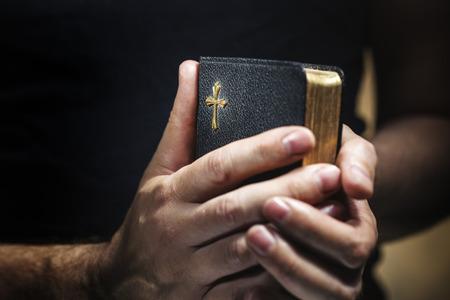 biblia: Hombre que sostiene una vieja peque�a biblia negro en sus manos. Corta profundidad de campo, la nitidez es en la cruz. Foto de archivo