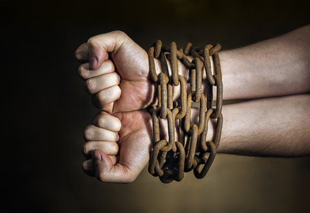 restraints: Hands of a man with a rusty chain around the wrists.