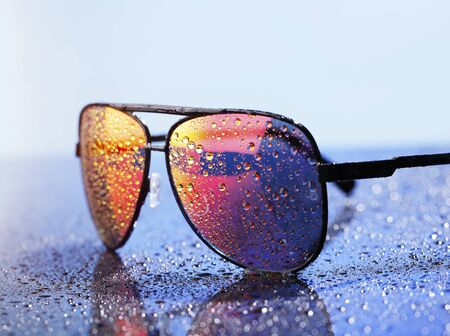 tinted glasses: Wet sunglasses on a wet reflective surface. Stock Photo