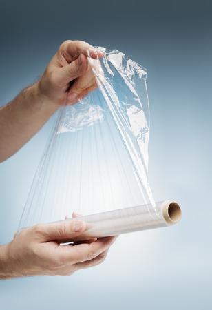 kunststoff: Man hält eine Rolle von Kunststofffolie, die typischerweise zur Abdichtung Lebensmittel verwendet.