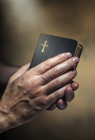 sharpness: Man holding an old small black bible in his hands. Short depth of field, the sharpness is in the cross.
