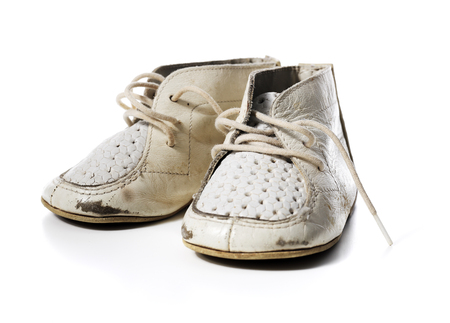 worn: Old worn vintage leather white baby shoes isolated on white with natural shadows.
