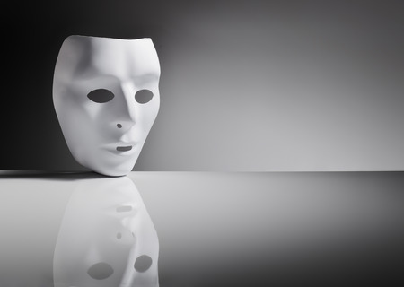 expressionless: White plastic mask on reflective surface.