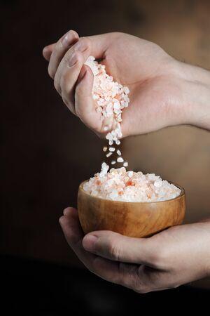 himalayan salt: Man pouring himalayan salt crystals from his hand.