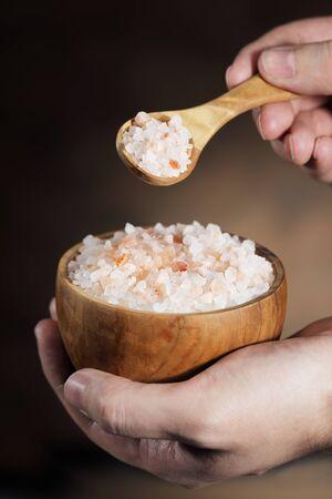 himalayan salt: Himalayan salt, wooden spoon and bowl.