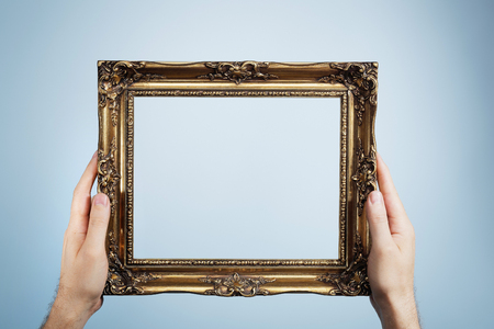 oldstyle: Man holding an antique look golden picture frame in his hands.