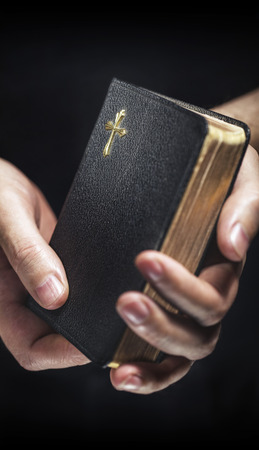 tightly: Man holding an old small black bible in his hands. Short depth of field, the sharpness is in the cross.